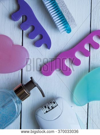 Accessories And Products For Foot Care. Epilator, Brush, Pumice, Soap, Gel, Toe Separator On A White