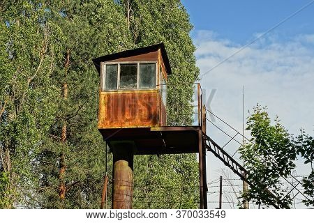 One Old Brown Rusty Iron Tower Observation Post With A Window On A Background Of Green Trees And Sky