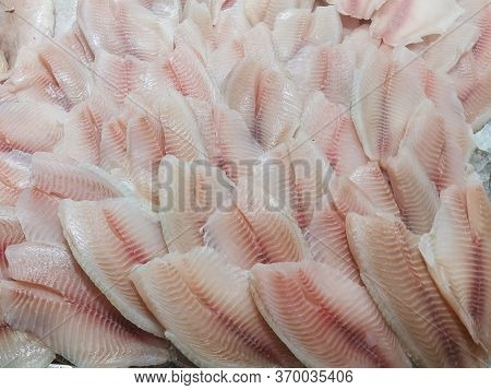 Fresh Fish Counter At The Market. Closeup Cod Fillet On Ice On A Market Counter. Useful Products For