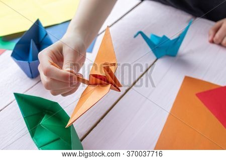A Girl Plays With An Origami Toy That She Made Herself. Origami Crane Made Of Colored Paper