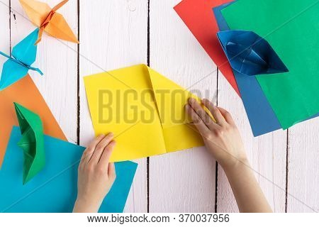A Girl Folds Colored Paper To Make Origami. A Girl Makes Origami On A Wooden Table
