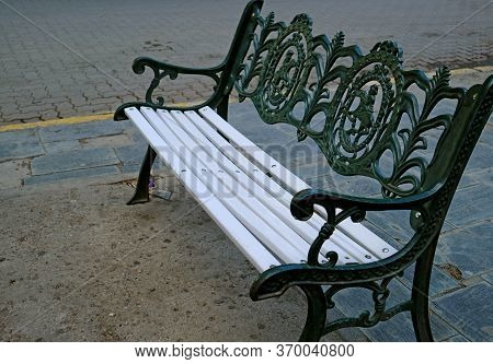 Empty White Wooden With Dark Green Wrought Iron Vintage Bench On The Square