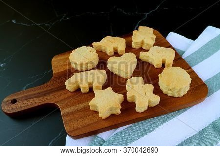 Homemade Delectable Cute Butter Cookies On Wooden Breadboard On Black Background