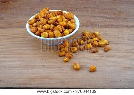Plateful Of Organic Corn Nuts With Sauce And Spilled Corn Nuts With Sauce On Wooden Background