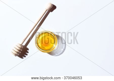 Honey In A Small Glass Plate On A White Background. Nearby Lies A Wooden Spoon