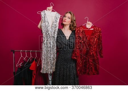 Charming Woman With Unsure Face Expression Holding Two Clothes Hangers In Store. Pretty European Gir