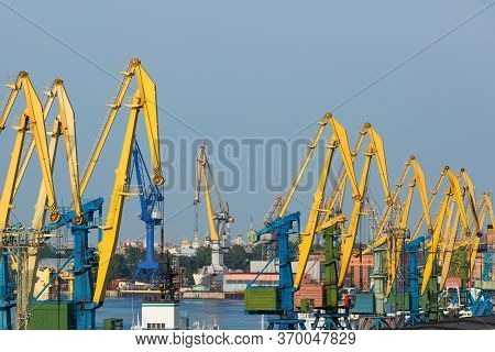 Industrial Landscape. Port Cranes Of Yellow And Blue Colors. Cargo Loading At The Port.