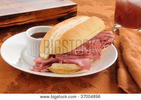 A roast beef sandwich au jus with a drink poster