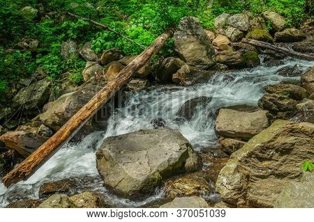 Water Rushing Downstream From The Waterfall Cascading Through The Rocks And Boulders And Flowing Und