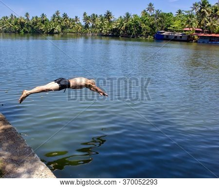 A French Man Dive In Shorts In The Backwater Of Allepey