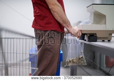 Bank employees using money counting machine while sorting and counting small iron banknotes inside bank vault. Large amounts of money in the bank