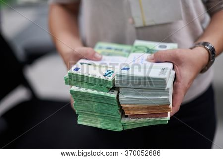 Bank employees holding a pile of paper banknotes while sorting and counting inside bank vault. Large amounts of money in the bank