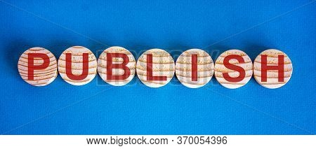 The Word 'publish' On Wooden Circles On Blue Table. Beautiful Background, Copy Space.
