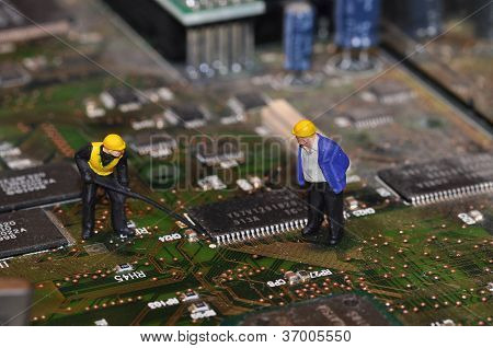 Two miniature workers on motherboard