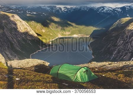 Tourists Tent Stands In The Mountains Near Famous Landmark - Troll Tongue Rock Or Trolltunga. Sunris