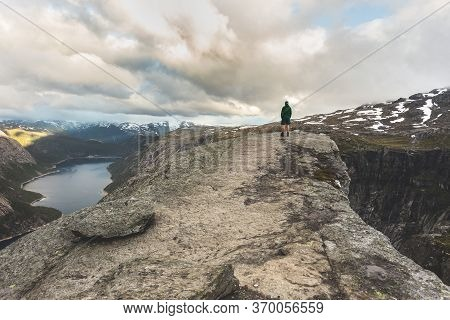 Tourist Stands Alone On Troll Tongue Rock. Famous Natural Landmark In Vestland County, Norway - Trol