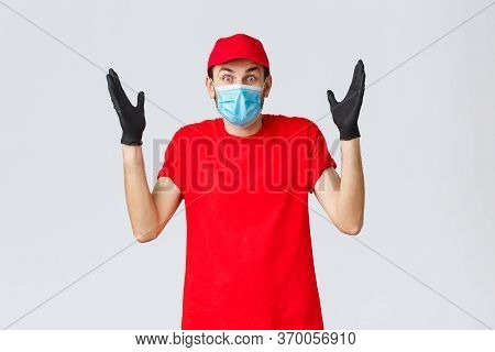 Covid-19, Self-quarantine, Online Shopping And Shipping Concept. Surprised And Confused Delivery Guy