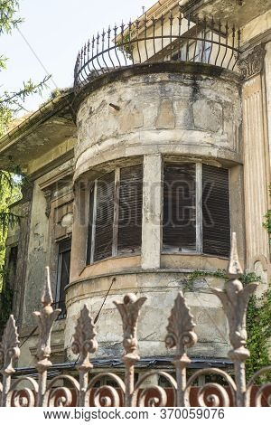 Facade Of An Abandoned Old House With Ruined Windows And A Terrace Behind A Rusty Patterned Fence Ag