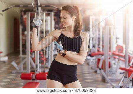 Woman In Fitness Wear Showing Her Biceps. Fitness Female Looking At Her Arm During Workout In Gym, L