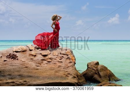 Beautiful Pregnant Woman In Flying Long Red Dress Poses On A Huge Rock Next To The Ocean In Seychell