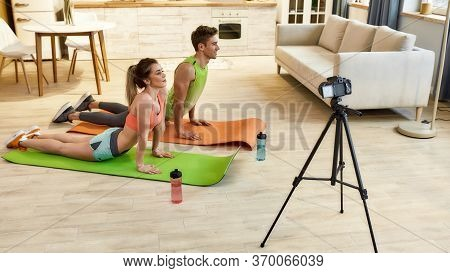 Young Couple In Sportswear Recording Video Blog Or Vlog About Healthy Lifestyle On Camera While Doin