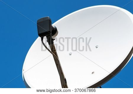 Old White Satellite Dish And A Television Antenna With Rust Against A Blue Sky