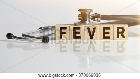 Fever The Word On Wooden Cubes, Cubes Stand On A Reflective White Surface, On Cubes - A Stethoscope.