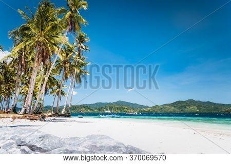 Ipil Beach With Coconut Palm Trees, Sandy Beach And Blue Ocean. El Nido, Palawan, Philippines