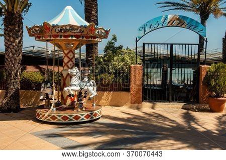 Torre De La Horadada, Valenciana, Spain - June 03 2020 : Childrens Roundabout Outside Vistamar Resta