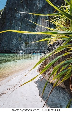 El Nido, Palawan, Philippines. Tropical Sandy Beach With Exotic Foliage Plants Surrounds By Karst Li