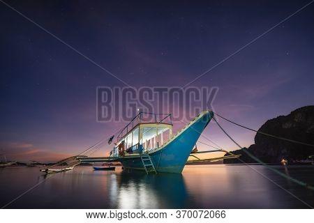 Banca Boat At Corong Beach Illuminated In Twilight Lit By Last Sunset Light, El Nido, Palawan, Phili