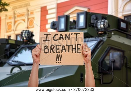 Cardboard Protest Poster Hold Hand With Message I Can't Breath On Background Armored Military Vehicl