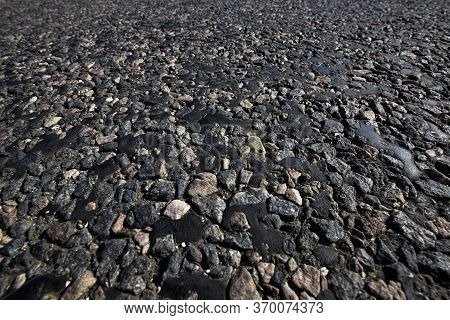 Part Of The Paved Road, Close-up On The Road Drenched In Black Resin, Which Emerges Through The Ston