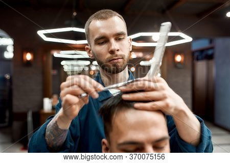 Close Up Of Young Professional Barber With Scissors And Hair Comb In Hands Making Haircut For His Cl
