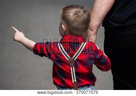 Curious Boy In A Plaid Shirt With Suspenders On Jeans