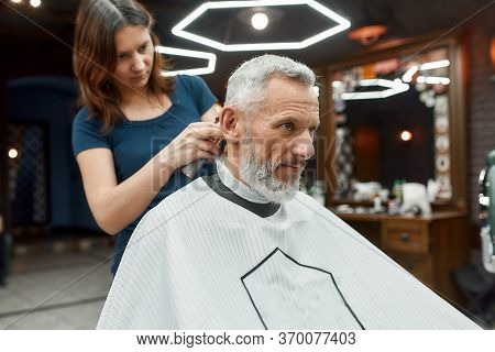 Handsome Mature Bearded Man Sitting In Barbershop Chair While Female Barber Working With Hair Clippe