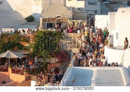 Santorini, Greece - July 18 2019: Beautiful Village Of Oia Crowded Full Of Tourists For The Sunset,