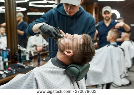 Mustache Correction. Barber Cutting Mustache Of His Client With Electrical Raser. Young Man Visiting