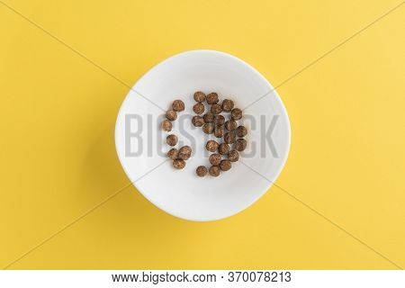 White Bowl With Few Chocolate Corn Cereal Balls On Yellow Background, Top-down View. Modern Fresh Br