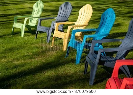 Colorful Plastic Adirondack Chairs Lined Up On The Grass Of A Yard In Sunlight And Shadows On A Summ
