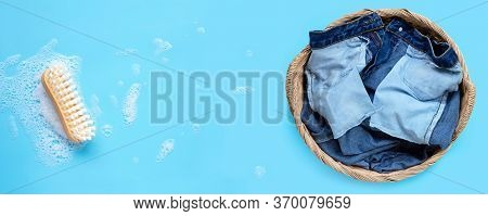 Jeans In Laundry Basket With Wooden Brush For Cleaning Clothes On Foam Of Powder Detergent Water Dis