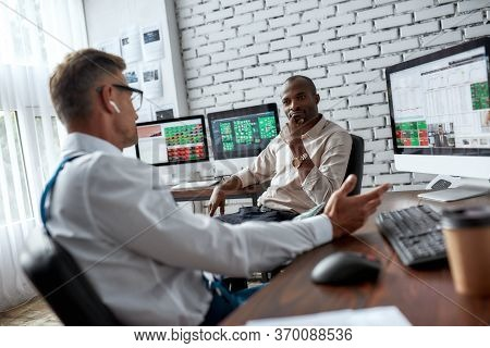 Two Diverse Colleagues Traders Talking To Each Other While Sitting In The Office In Front Of Multipl