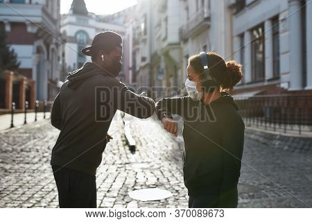 Elbow Bumping. Young African Couple Of Runners In Medical Protective Masks Bumping Elbows Instead Of