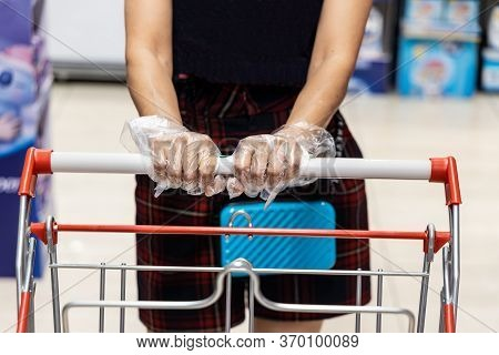 Close-up  Of Woman Wearing Disposable Gloves Pushing Shopping Cart Shopping