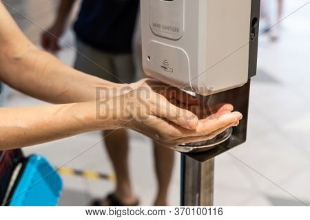 Person Sanitizing Hands With Liquid Gel From Public Sanitizing Machine