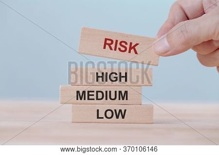 Hand Holding Chooses Wooden Block Cubes With Risk Word. Risk Management Concept.