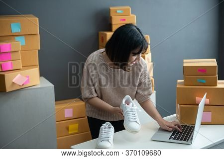 Asian Smiling Girl Using Smartphone To Shoot White Sneaker Posted For Sale On The Internet.startup S