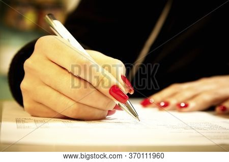 A Girl With Beautiful Red Nails Fills A Document With A Ballpoint Pen. Female Hand Holds A Ballpoint