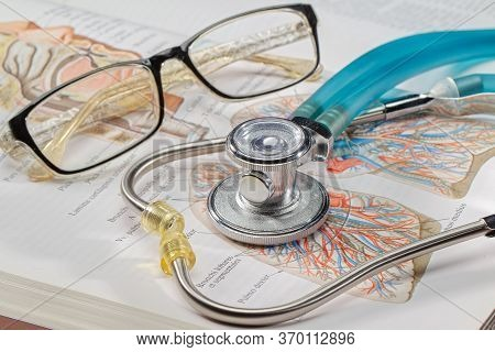 Concept Distance Education. Stethoscope And Glasses On The Background Of The Open Pages Of The Atlas
