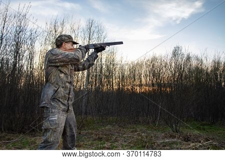 A Hunter Takes Aim With A Double Barrelled Rifle At Dusk In A Spring Forest